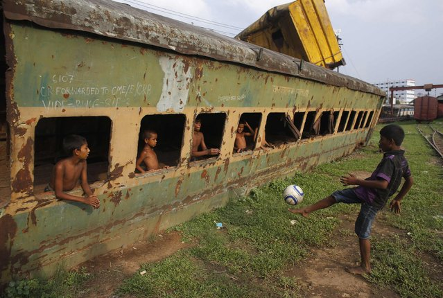 Children play football in front of an abandoned train compartment next to a railway track in Dhaka, in this May 29, 2014 file photo. (Photo by Andrew Biraj/Reuters)