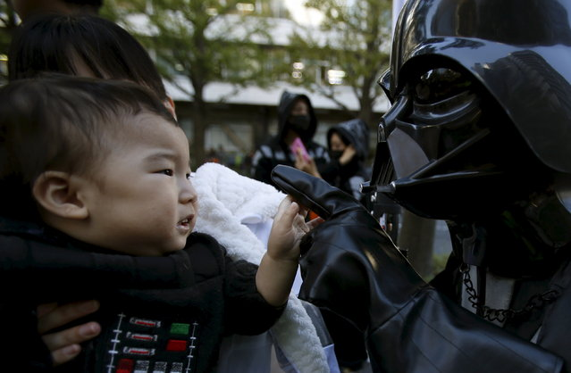 """A boy looks at his father dressed up as Darth Vader from """"Star Wars""""during a Star Wars parade, which is part of a Halloween parade in Kawasaki, south of Tokyo, October 25, 2015. (Photo by Yuya Shino/Reuters)"""