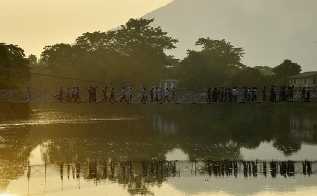 Forest officials crossing a hanging bridge after inspecting the preparation for the reopening of the Pobitora Wildlife Sanctuary for the tourist season in Morigaon district of Assam state, India, 30 September 2016. Pobitora Wildlife Sanctuary and Kaziranga National park will be reopened for tourist on 1st of October 2016, which in one month advance then the previous seasons. Both these parks are famous for Indian one horned Rhinos. (Photo by EPA/Stringer)