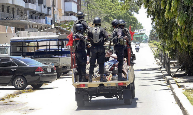 In this photo taken Monday, October 26th, 2015 and made available Wednesday, October 28th, 2015, police special forces ride in the back of a vehicle with unidentified men they had arrested, in the Darajani area of Stone Town, Zanzibar, a semi-autonomous island archipelago of Tanzania. (Photo by AP Photo)