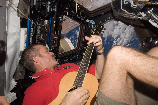 Canadian Space Agency astronaut Chris Hadfield strums his guitar in the ISS's Cupola on December 25, 2012. Hadfield, a long-time member of an astronaut band called Max Q, later joined with the other five Expedition 34 crew members in a more spacious location to provide an assortment of Christmas carols for the public. (Photo by NASA/The Atlantic)