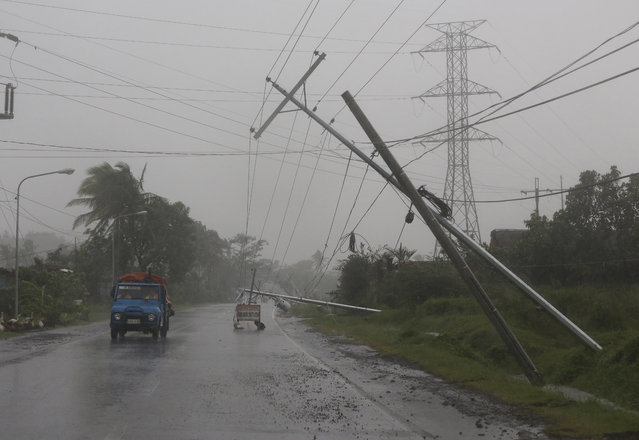 Motorists pass by toppled electrical posts due to strong winds brought by Typhoon Hagupit in Camalig, Albay province, eastern Philippines on Sunday, December 7, 2014. (Photo by Aaron Favila/AP Photo)