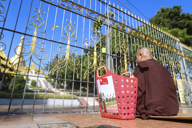 "A ""Vote NLD"" sticker with the image of Myanmar leader Aung San Suu Kyi is pasted on a basket next to a Buddhist nun praying outside the Shwedagon pagoda in Yangon, Myanmar on Thursday, November 5, 2020. Myanmar's citizens go to the polls Sunday, Nov. 8, in an effort to sustain the fledgling democracy they helped install just five years ago. (Photo by Thein Zaw/AP Photo)"