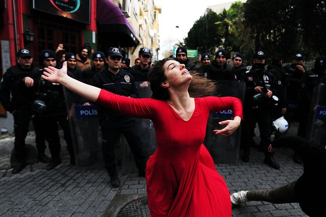 A woman dances in front of riot police during a demonstration on December 9, 2014 in the Kadikoy neighborhood of Istanbul against the eviction of a squatted building. An abandoned building was squatted and converted into a social meeting center by activists following last years Gezi Park protests. Police were to evict the squat on December 9. (Photo by Ozan Kose/AFP Photo)