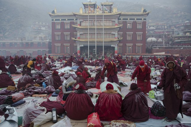 Hot tea is distributed to monks and nuns gathering in sub-zero temperatures at Buddhist laymen lodge, where thousands of people gather for morning chanting session, during the Utmost Bliss Dharma Assembly, the last of the four Dharma assemblies at Larung Wuming Buddhist Institute in remote Sertar county, Garze Tibetan Autonomous Prefecture, Sichuan province, China November 1, 2015. (Photo by Damir Sagolj/Reuters)