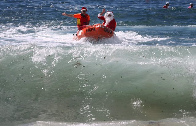 A man dressed as Santa Claus waves as he arrives in an inflatable rescue boat (IRB), as part of Christmas celebrations for the Coogee Surf Lifesaving Club, at Sydney's Coogee Beach December 14, 2014. (Photo by David Gray/Reuters)