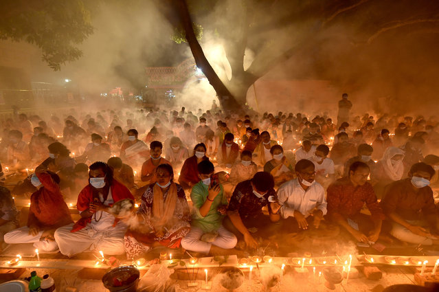 Hindu devotees sit for prayer with burning incense and light oil lamps during the Rakher Upobash, a religious fasting festival, at a temple in Narayanganj district on the outskirts of Bangladeshi capital Dhaka, on November 7, 2020. (Photo by Xinhua News Agency/Rex Features/Shutterstock)