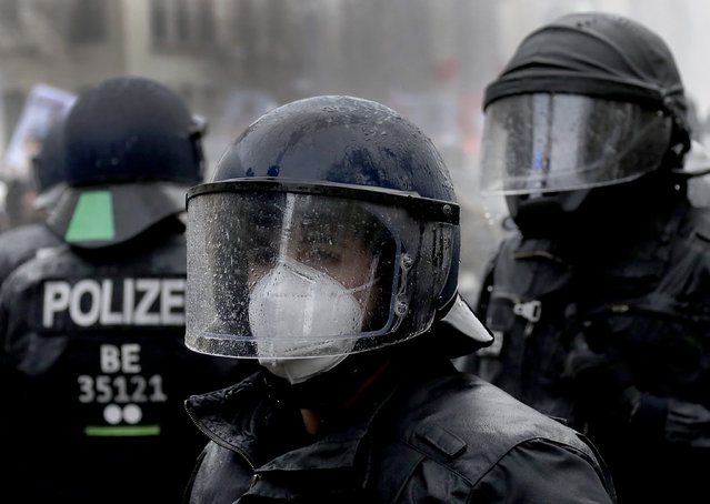 A police person wears a face mask under a helmet after beeing hit by a water canon during a violent protest ralley in a road between the Brandenburg Gate and the Reichstag building, home of the German federal parliament, in Berlin, Germany, Wednesday, November 18, 2020 against the coronavirus restrictions in Germany. Police in Berlin have requested thousands of reinforcements from other parts of Germany to cope with planned protests by people opposed to coronavirus restrictions. (Photo by Michael Sohn/AP Photo)