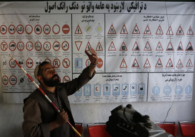 An instructor explains traffic signs during a lesson at a driving school in Kabul August 11, 2014. (Photo by Mohammad Ismail/Reuters)
