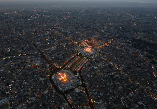 This aerial photo shows Shiite faithful pilgrims gather between, the holy shrine of Imam Hussein, top, and the holy shrine of Imam Abbas, bottom, for Arbaeen in the Shiite holy city of Karbala, 50 miles (80 kilometers) south of Baghdad, Iraq, Saturday, December 13, 2014. The holiday marks the end of the forty day mourning period after the anniversary of the 7th century martyrdom of Imam Hussein, the Prophet Muhammad's grandson. (Photo by Hadi Mizban/AP Photo)