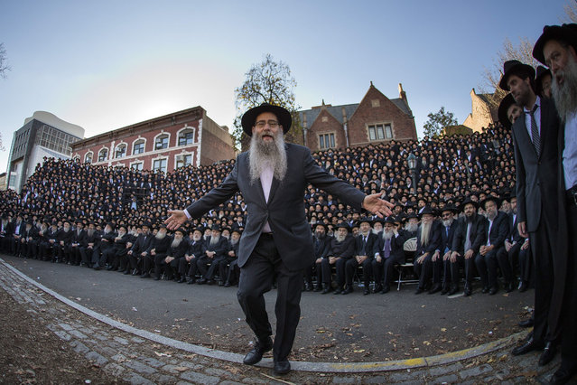 A rabbi moves people and members of the media as thousands of Hasidic rabbis from 86 countries prepares for an official group photo near Chabad-Lubavitch headquarters in the Brooklyn borough of New York, Sunday, November 8, 2015. The group is in New York for the International Conference of Chabad-Lubavitch Emissaries, an annual event aimed at reviving Jewish awareness and practice around the world. (Photo by Andres Kudacki/AP Photo)