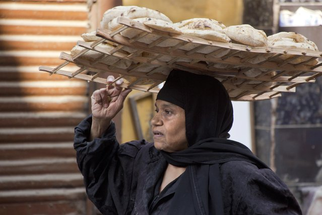 An Egyptian carries bread tray in the neighborhood of El-Gamaliah, in Cairo, Egypt, Friday, October 7, 2016. Egypt is moving ahead with a reform program expected to weaken the pound drastically but also hopefully pave the way for sustainable economic growth that creates jobs for a surging population. (Photo by Amr Nabil/AP Photo)