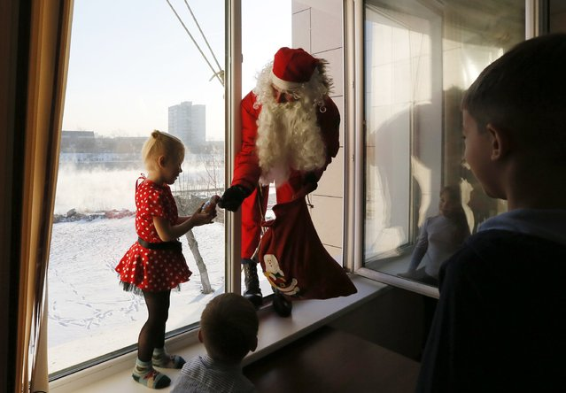 """Alexei Trifonov, a member of the """"Rescuer"""" state regional service, dressed as Santa Claus, gives a sweet to a girl as he congrastulates employees of the Russian Emergencies Ministry and their children ahead of New Year and Christmas celebrations in Krasnoyarsk, Siberia December 24, 2014. (Photo by Ilya Naymushin/Reuters)"""