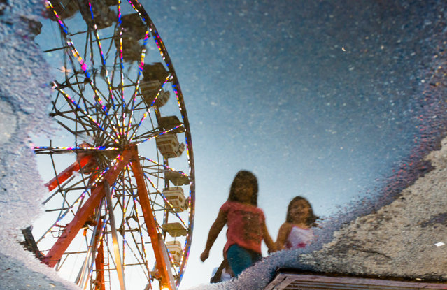 A colorful ferris wheel and two girls are reflected in a puddle on Tuesday, June 3, 2014 in Langley Park Maryland at a carnival sponsored by The Langley Park Boys and Girls Club. It is located near New Hampshire Ave. and Riggs Road and is running until June 15th. (Photo by Sarah L. Voisin/The Washington Post)