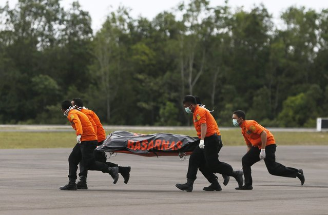 Search and rescue team members run as carry the dead body of a passenger onboard AirAsia flight QZ8501 at Iskandar airbase in Pangkalan Bun, Indonesia, December 31, 2014. A sonar image showing a large, dark object on the sea bed is believed to be a missing AirAsia plane, an official with Indonesia's search and rescue agency said on Wednesday after bodies and debris were found in the area. (Photo by Reuters/Beawiharta)