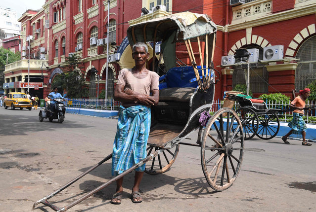 Mohammad Ashgar, 65, an Indian rickshaw puller, poses for a photograph next to his rickshaw in Kolkata on April 21, 2018. A mainstay of 19 th century transportation options, the hand- pulled rickshaw survives in India only in Kolkata after being outlawed elsewhere. The local puller's union puts the number of pullers in the city at 3,000. The union has resisted all previous attempts to ban their livelihood, previously organising mass protests of their members against moves to stamp out the practice. (Photo by Dibyangshu Sarkar/AFP Photo)