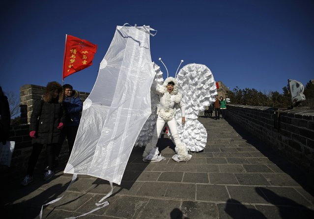 Chinese artist Kong Ning wears a costume symbolizing a butterfly, which is decorated with 365 masks on its wings to represent the number of days in a year, while holding a large kite in the shape of a mask during her performance art at the Badaling section of the Great Wall on the outskirts of Beijing January 1, 2015. (Photo by Kim Kyung-Hoon/Reuters)