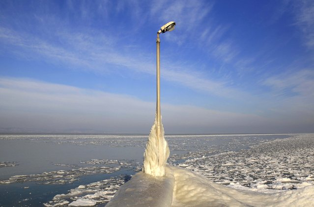 A lamp post covered with ice is seen on a pier on the frozen Lake Balaton in Zamardi, west of Budapest, December 31, 2014. (Photo by Bernadett Szabo/Reuters)