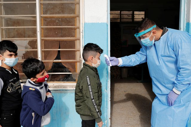 A medical team member wearing a protective suit checks a student's temperature during testing for the coronavirus disease (COVID-19) at a school in Baghdad, Iraq on December 14, 2020. (Photo by Thaier al-Sudani/Reuters)