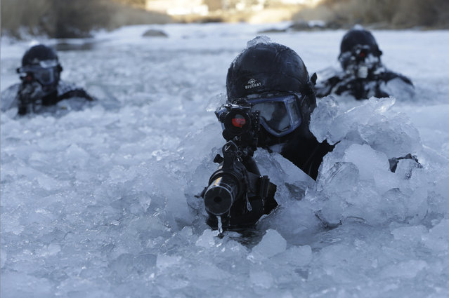 South Korea's Amry Special Warfare Command (SWC) soldiers aim their machine guns in a frozen river during a winter exercise in Pyeongchang, South Korea, Thursday, January 8, 2015. About 200 SWC soldiers participated in this routine two-week winter drill. (Photo by Ahn Young-joon/AP Photo)