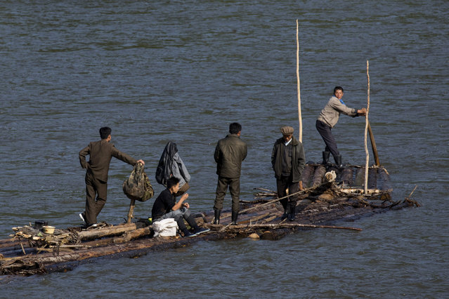 In this August 30, 2017 photo, North Korean men ride a makeshift raft made of fastened logs down the Yalu river that divides North Korea from the Chinese border town of Linjiang in northeastern China's Jilin province. North Korea is changing, quietly but powerfully, with the rise of the young ruler Kim Jong Un extending even to those secret trails, where business has turned bad for the small-time smugglers who long dominated the border. (Photo by Ng Han Guan/AP Photo)