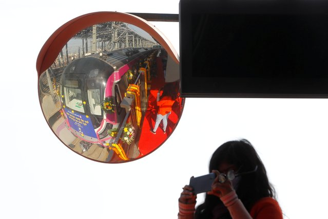A girl takes a picture of the first fully automated driverless Delhi metro train during its inauguration in New Delhi, India, December 28, 2020. (Photo by Adnan Abidi/Reuters)