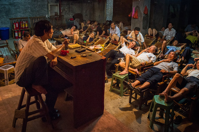 """""""The storyteller"""". In Sichuan province, China, the tea house still plays a vital role in the daily life: here people relax during a storytelling session. Honourable mention: Travel. (Photo by Aimin Wang/SIPA Contest)"""