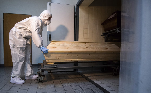 """Employee Niklas Grube pushes a coffin into a cooling chamber at the crematorium """"Die Feuerbestattungen Celle"""", in Celle, Germany, Wednesday, January 13, 2021.  The crematorium in Celle has seen an increase in cremations of Corona deceased since November 2020. (Photo by Julian Stratenschulte/dpa via AP Photo)"""