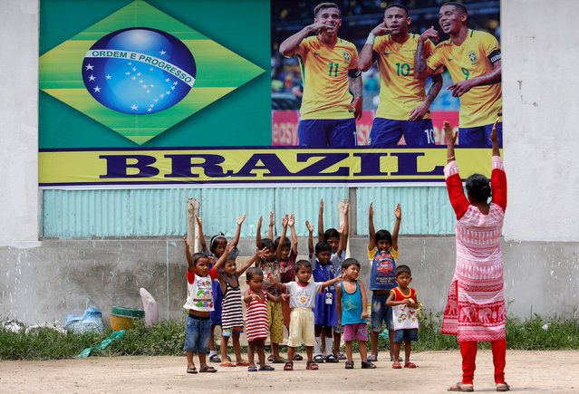 Children of a municipal school exercise in front of a banner of Brazil's soccer players pasted on a wall in Kolkata, ahead of the FIFA World Cup, in Kolkata, India June 12, 2018. (Photo by Rupak De Chowdhuri/Reuters)
