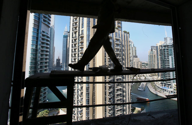 In this Aug. 10, 2015 photo, a worker walks on wooden scaffolding while fixing a window frame at a construction site in the Marina neighborhood of Dubai, United Arab Emirates. Armies of low-paid migrant workers, many of them from the Indian Subcontinent, leave behind families and travel to Dubai to build soaring towers like those in the Marina. While the wages they come for offer hope of a better life, they are far too meager for most to ever dream of calling the Marina they built home. (Photo by Kamran Jebreili/AP Photo)