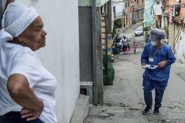 """A resident stands in her doorway as a member of the """"Bora Testar"""" or Let's Test project, walks through the the Paraisopolis neighborhood of Sao Paulo, Brazil, Friday, September 11, 2020. The project plans to test up to 600 people for COVID-19 in the low income neighborhood, and to expand to other vulnerable communities in the country, financed by crowdfunding and donations. (Photo by Carla Carniel/AP Photo)"""
