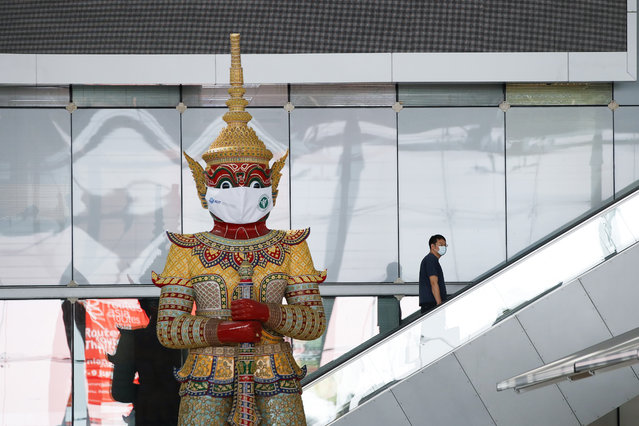 A traveler wearing a protective face mask rides an escalator past a Ramayana Giant Guardian statue with a large protective mask at the Suvarnabhumi International Airport amid a new wave of the coronavirus disease (COVID-19) pandemic in Bangkok, Thailand, 05 January 2021. The Thai government ordered a nationwide partial business shutdowns for 28 'red zones' provinces including Bangkok as part of stricter measures to curb the new wave of the infectious disease. Travelers flying between Thai provinces could face additional health screening, and international flights from the UK have been put on hold. Thai authorities recorded 745 new cases with 709 being local infections, making it the highest number of daily infections since the start of the pandemic. (Photo by Diego Azubel/EPA/EFE)