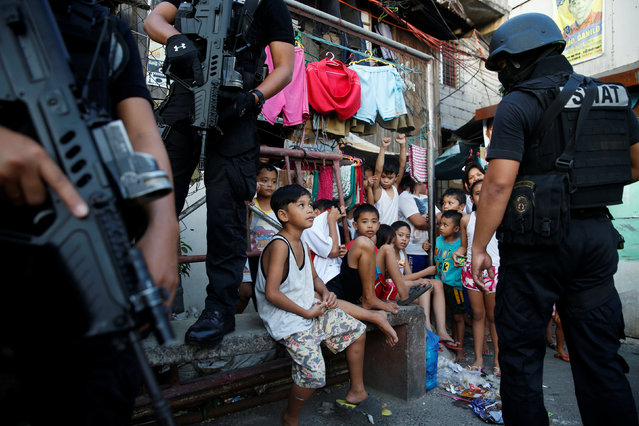Members of Philippine National Police SWAT team stand guard near residents during an anti-drugs operation, in Pasig, Metro Manila in the Philippines, November 9, 2016. (Photo by Erik De Castro/Reuters)