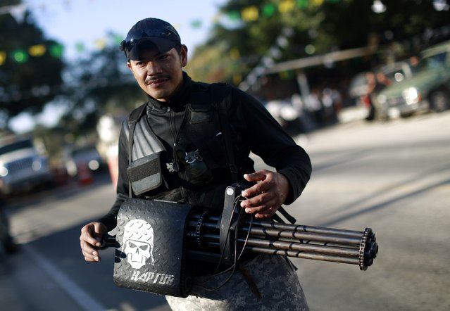 A member of the Community Police of the FUSDEG (United Front for the Security and Development of the State of Guerrero) poses with a weapon during events to mark the first anniversary of the force's operations in Ocotito, January 23, 2015. (Photo by Jorge Dan Lopez/Reuters)