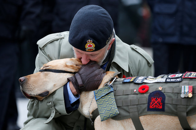 A veteran embraces his service dog during Remembrance Day ceremonies at the National War Memorial in Ottawa, Ontario, Canada, November 11, 2016. (Photo by Chris Wattie/Reuters)