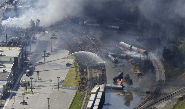 The wreckage of a train is pictured after an explosion in Lac Megantic July 6, 2013. Several people were missing after four tank cars of petroleum products exploded in the middle of a small town in the Canadian province of Quebec early on Saturday in a fiery blast that destroyed dozens of buildings. (Photo by Mathieu Belanger/Reuters)