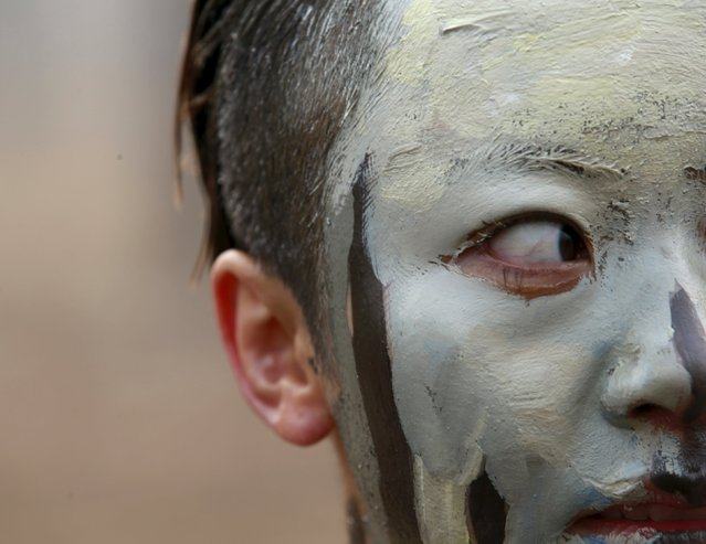"""A model painted in camouflage colours to blend in with the background waits to pose for Chinese artist Liu Bolin's artwork """"Dongji"""", or Winter Solstice, on the second day after China's capital Beijing issued its second ever """"red alert"""" for air pollution, in Beijing, China, December 20, 2015. (Photo by Kim Kyung-Hoon/Reuters)"""