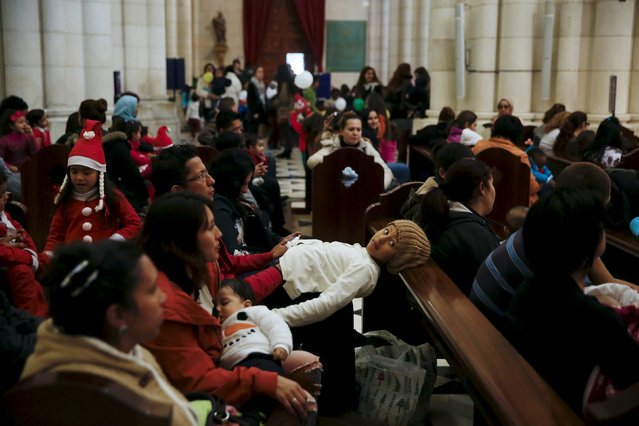 Children wait for the start of a distribution of free toys for low-income families and a picture on the lap of one of the Three Wise Men at Almudena Cathedral in Madrid, Spain, December 22, 2015. (Photo by Susana Vera/Reuters)