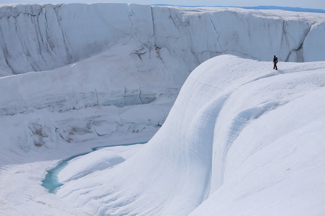 Sarah Das from the Woods Hole Oceanographic Institution looks at a canyon created by a meltwater stream on July 16, 2013 on the glacial ice sheet. (Photo by Joe Raedle/Getty Images via The Atlantic)