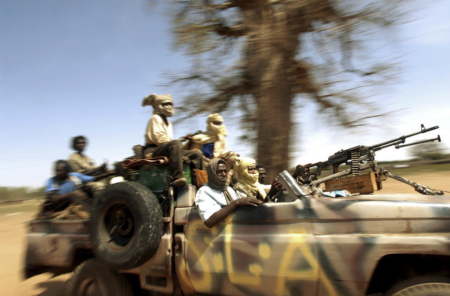 Soldiers with the Sudanese Liberation Army parade their weapons during a rebel conference for the SLA  in Haskanita, in SLA territory in Darfur, Sudan, October 2005. (Photo by Lynsey Addario)
