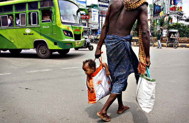 A man carries his child in a bag as he crosses a street in Bhubaneswar, India, on August 9, 2013. (Photo by Biswaranjan Rout/Associated Press)