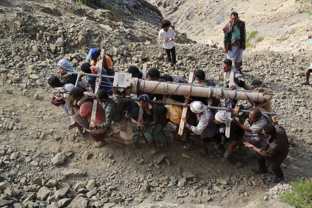 Fighters of the pro-government Popular Resistance Committees militia carry a cannon as they transport it in parts to Yemen's southwestern war-torn city of Taiz December 26, 2015. (Photo by Reuters/Stringer)