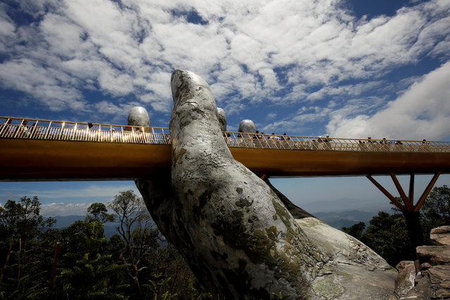 Tourists stand on Gold Bridge on Ba Na hill near Danang city, Vietnam on August 1, 2018. (Photo by Reuters/Kham)