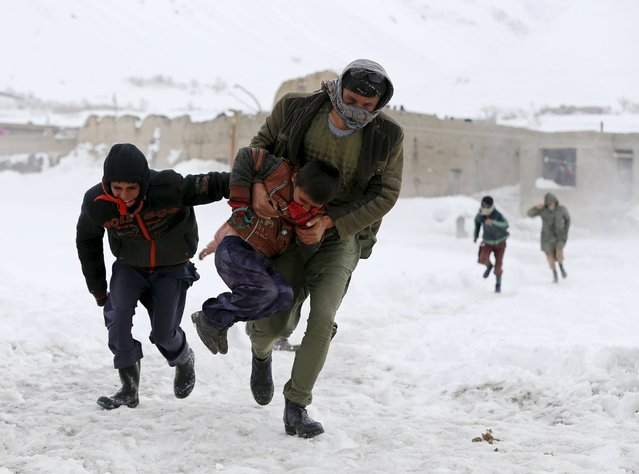 Afghan survivors of an avalanche run to get relief goods distributed by an Afghan army helicopter in the Paryan district of Panjshir province, north of Kabul, Afghanistan March 1, 2015. (Photo by Omar Sobhani/Reuters)