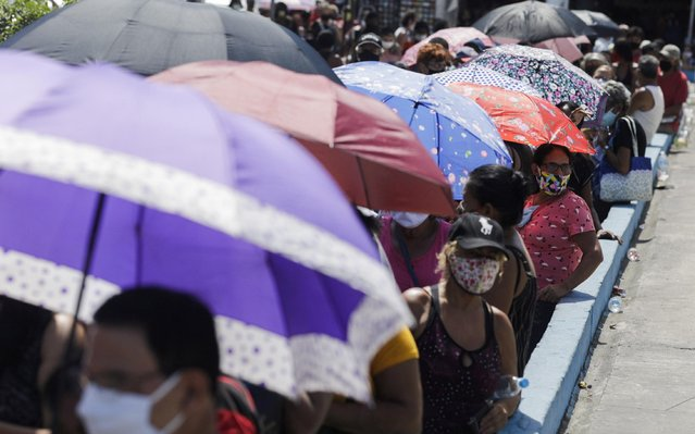 Elderly people wait in line to receive a dose of the Sinovac's CoronaVac coronavirus disease (COVID-19) vaccine, during a vaccination day for 65-year-old and older citizens in Duque de Caxias near Rio de Janeiro, Brazil on March 29, 2021. (Photo by Ricardo Moraes/Reuters)