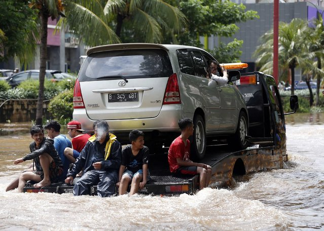 People ride on the back of a truck ferrying a vehicle down a flooded street after continuous heavy seasonal rains inundated many parts of Jakarta February 10, 2015. (Photo by Darren Whiteside/Reuters)