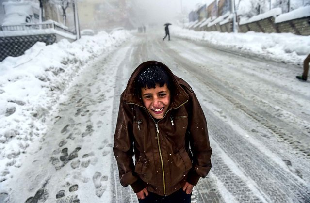 A Kurdish boy protects himself against the cold as heavy snow fall hits the city of Sirnak, southeastern Turkey, on January 1, 2016. Tensions are running high throughout Turkey's restive southeast as security forces impose curfews in several towns including Cizre in a bid to root out Kurdistan Workers' Party (PKK) rebels from urban centres. (Photo by Bulent Kilic/AFP Photo)