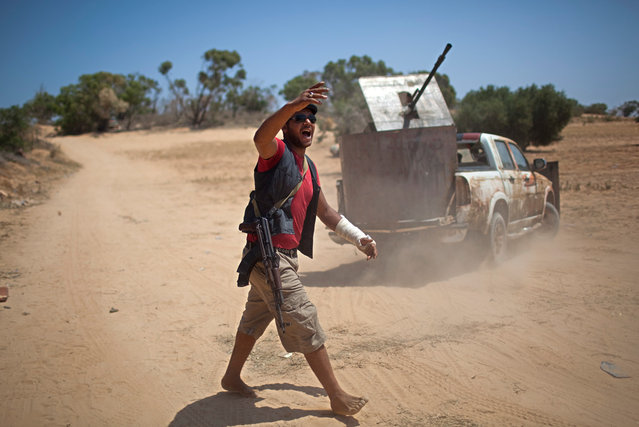 A rebel fighter in front of an armored technical gives orders to comrades at the front line between the rebels and pro-Qaddafi forces, 25 km west of Misurata, on May 26, 2013. (Photo by Rodrigo Abd/AP Photo)