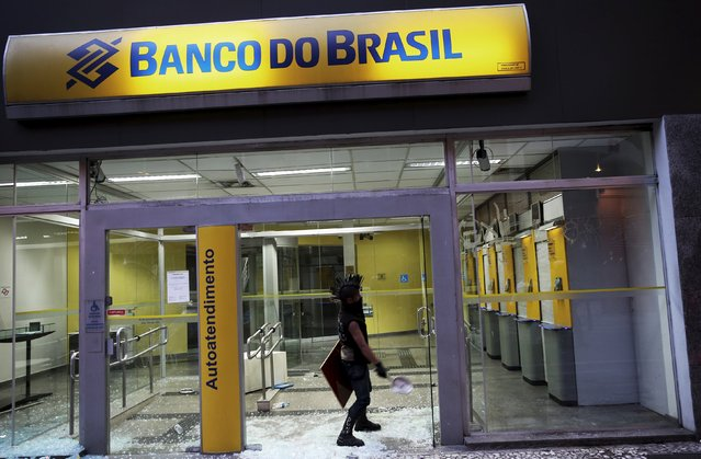 A demonstrator attacks a Brasil bank branch during a protest against fare hikes for city buses in Sao Paulo, Brazil, January 8, 2016. (Photo by Nacho Doce/Reuters)