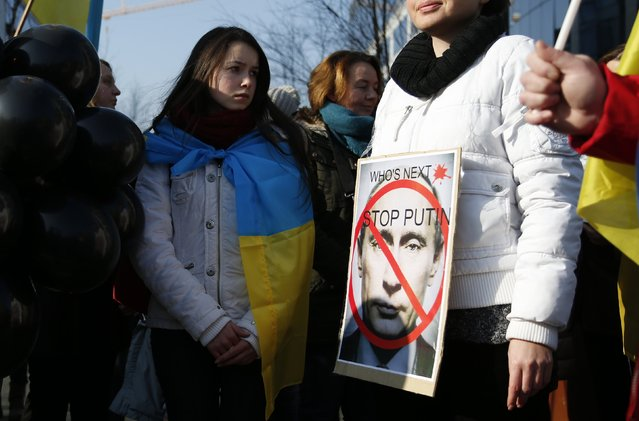 A demonstrator displays a defaced picture of Russian President Vladimir Putin during a protest seeking the release of Ukrainian army pilot Nadezhda (Nadia) Savchenko, outside a meeting of European Union leaders in Brussels February 12, 2015. (Photo by Francois Lenoir/Reuters)